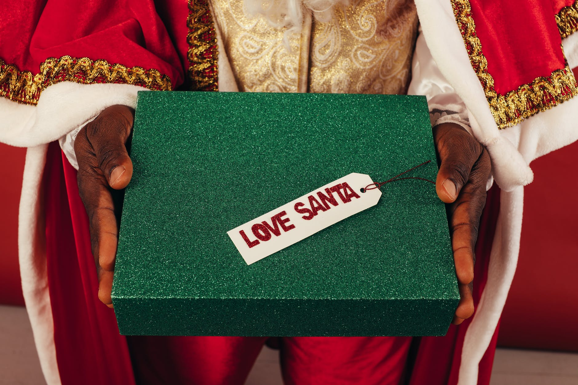 person in santa outfit holding a gift box