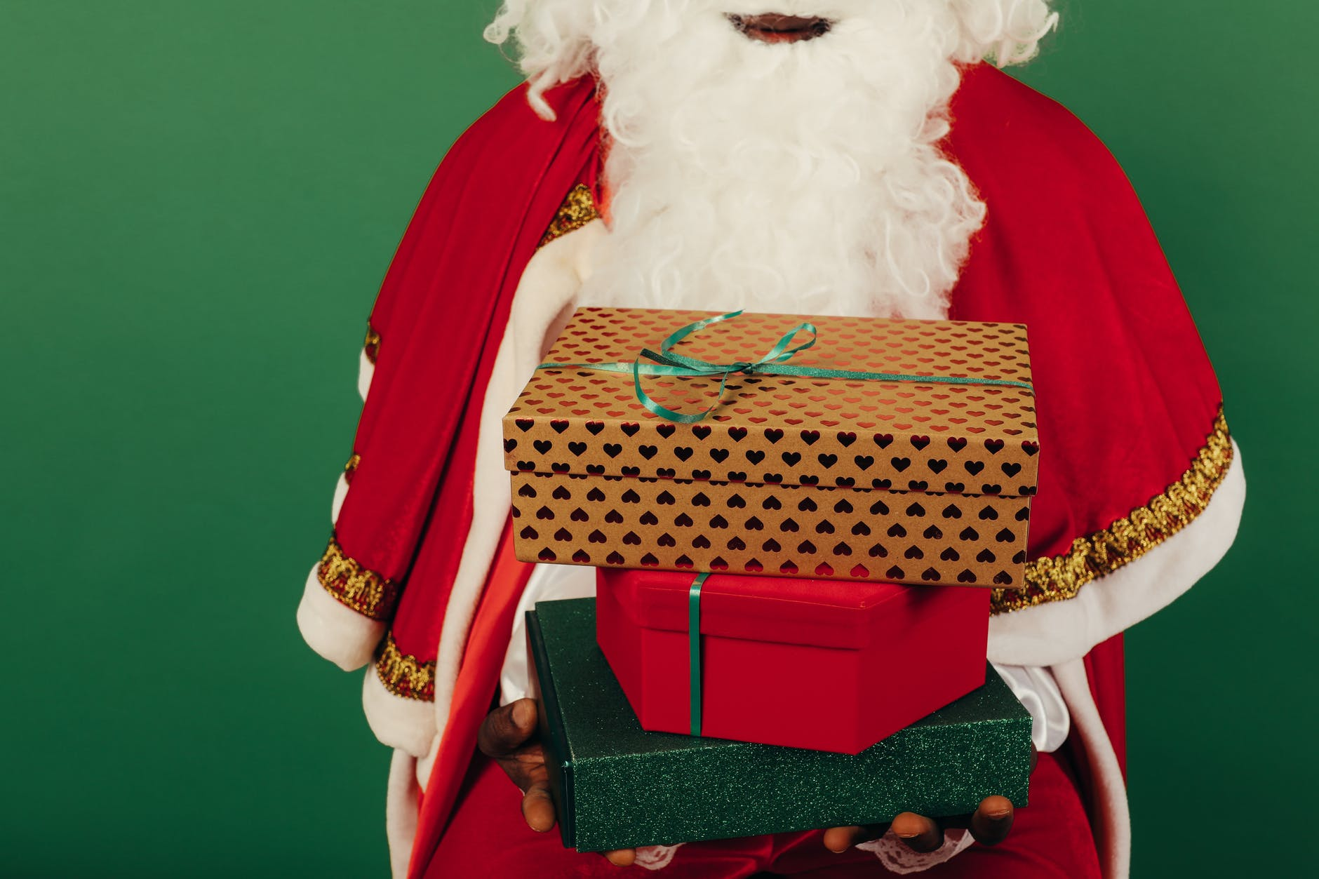 person wearing santa claus outfit while holding christmas gifts
