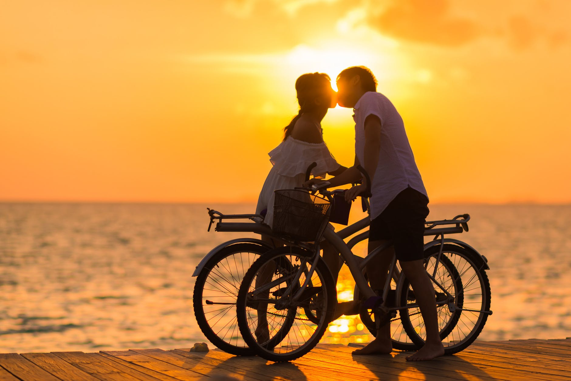 photography of man wearing white t shirt kissing a woman while holding bicycle on river dock during sunset